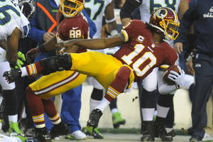 Photo - Washington Redskins quarterback Robert Griffin III flies through the air as he is knocked out of bounds during the first half of an NFL wild card playoff football game against the Washington Redskins in Landover, Md., Sunday, Jan. 6, 2013. (AP Photo/Richard Lipski)
