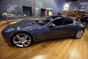 Photo - FILE - This Nov. 18, 2010 file photo shows the Fisker Automotive's Fisker Karma, a sports luxury plug-in hybrid car at the 2010 Los Angeles Auto Show in Los Angeles. A Delaware bankruptcy judge on Friday ordered a competitive auction for the assets of Fisker Automotive, rejecting a proposal by a group led by Hong Kong billionaire Richard Li to assume control of the failed electric auto manufacturer in a private sale.  (AP Photo/Damian Dovarganes, File)