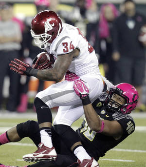 Photo - Oregon defender Rodney Hardick, right, pulls down Washington State running back Teondray Caldwell during the second half of an NCAA college football game in Eugene, Ore., Saturday, Oct. 19, 2013. Oregon won 62-38.(AP Photo/Don Ryan)