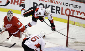 Photo - Ottawa Senators left wing Clarke MacArthur (16) passes the puck to right wing Bobby Ryan (6) who scores on Detroit Red Wings goalie Jonas Gustavsson during the third period of an NHL hockey game in Detroit, Wednesday, Oct. 23, 2013. (AP Photo/Carlos Osorio)