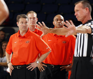 Photo - Oklahoma State coaches Travis Ford, left, and Butch Pierre, right ,get an explanation on a foul call during the second half of an NCAA college basketball game at the 76 Classic in Anaheim, Calif., Friday, Nov. 26, 2010. (AP Photo/Christine Cotter)