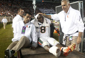 Photo - Miami running back Duke Johnson is consoled as he is taken off the field after injuring his foot during the third quarter of an NCAA college football game against Florida State on Saturday, Nov. 2, 2013, in Tallahassee, Fla. (AP Photo/Phil Sears)