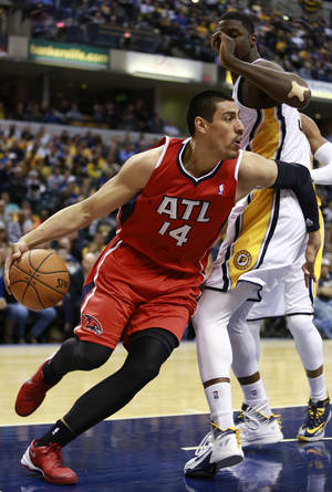Photo - Atlanta Hawks center Gustavo Ayon (14) works his way around Indiana Pacers center Roy Hibbert during the first half of an NBA basketball game in Indianapolis, Tuesday, Feb. 18, 2014. (AP Photo/R Brent Smith)