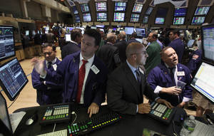 photo -   Specialists Robert Canzani, left, and Henry Becker, second from right, work at their posts on the floor of the New York Stock Exchange Thursday, June 28, 2012. Stocks dropped sharply Thursday after the Supreme Court upheld the central provision of President Barack Obama's health care overhaul, a requirement that almost all Americans carry health insurance. (AP Photo/Richard Drew)