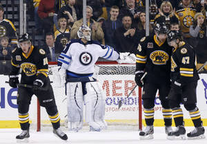 Photo - Winnipeg Jets' Ondrej Pavelec, center, stands in the goal as Boston Bruins' Johnny Boychuk (55) and Torey Krug (47) celebrate a goal by teammate Reilly Smith, left, in the third period of an NHL hockey game in Boston, Saturday, Jan. 4, 2014. The Bruins won 4-1. (AP Photo/Michael Dwyer)