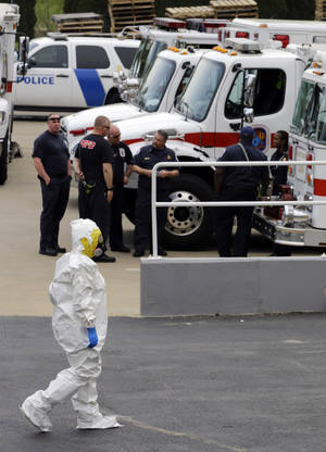 Photo - A Prince George's County, Md., firefighter dressed in a protective suit walks past emergency personnel into a government mail screening facility. AP Photo