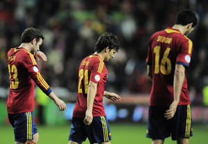photo - Spain's Juan Manuel Mata, David Silva and Sergio Busquets, left to right, lament at the end of the match during a Group I 2014 World Cup qualifying soccer match after Finland tied 1-1, at El Molinon stadium in Gijon, northern Spain on Friday, March 22, 2013.  (AP Photo/Alvaro Barrientos)