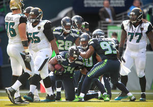 Photo - Seattle Seahawks players swarm to linebacker Bobby Wagner (54) after he intercepted a pass by Jacksonville Jaguars quarterback Chad Henne during an NFL football game in Seattle, Sunday, Sept. 22, 2013. (AP Photo/The Olympian, Tony Overman)