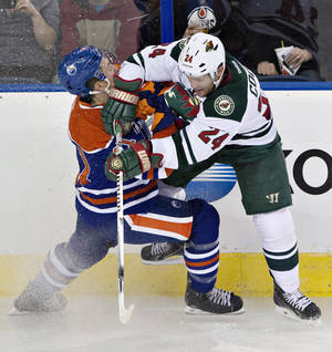 Photo - Minnesota Wild's Matt Cooke (24) checks Edmonton Oilers' Andrew Ference (21) during second period NHL hockey action in Edmonton, Canada, Thursday, Feb. 27, 2014. (AP Photo/The Canadian Press, Jason Franson)