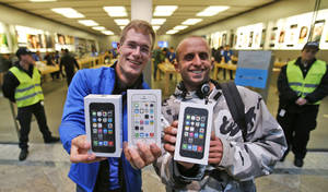 Photo - First customers of the Apple store in Oberhausen are all smile with their new iPhones in hand as they leave the store after the start of the new iPhone sale in Oberhausen, Germany, Friday, Sept. 20, 2013. (AP Photo/Frank Augstein)