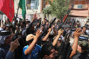 Photo - Iraqi Shiite tribal fighters raise their weapons and chant slogans against the al-Qaida inspired Islamic State of Iraq and the Levant (ISIL) in Baghdad's Sadr city, Iraq, Saturday, June 14, 2014. Thousands of Shiites from Baghdad and across southern Iraq answered an urgent call to arms Saturday, joining security forces to fight the Islamic militants who have captured large swaths of territory north of the capital and now imperil a city with a much-revered religious shrine. (AP Photo/Karim Kadim)