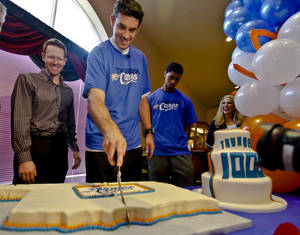 Photo - Oklahoma City Thunder general manager Sam Presti, left, watches Thunder player Nick Collison cut a cake at Ranchwood Nursing Home in Yukon on Nov. 27 during the team' 1,000th community appearance. Photo by Chris Landsberger,  The Oklahoman Archives