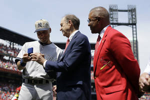 Photo - New York Yankees shortstop Derek Jeter, left, is presented with a pair of cufflinks by St. Louis Cardinals Bill DeWitt Jr., center, and former Cardinals Hall of Fame shortstop Ozzie Smith, right, during a ceremony before the start of a baseball game between the Yankees and Cardinals Monday, May 26, 2014, in St. Louis. (AP Photo/Jeff Roberson)
