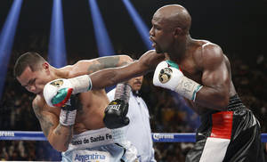 Photo - Floyd Mayweather Jr., right, connects with a right to the head of Marcos Maidana, from Argentina, in their WBC-WBA welterweight title boxing fight Saturday, May 3, 2014, in Las Vegas. (AP Photo/Eric Jamison)