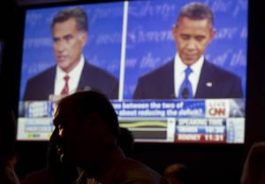Photo -   John Rossitto watches the first presidential debate between President Barack Obama and Republican presidential nominee Mitt Romney from a restaurant in San Diego, Wednesday, Oct. 3, 2012. (AP Photo/Gregory Bull)
