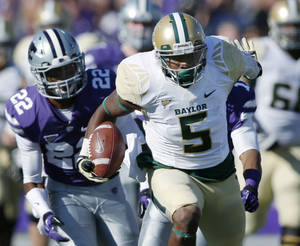Photo - Baylor wide receiver Antwan Goodley (5) runs with a reception for a touchdown as Kansas State defensive backs Randall Evans, obscured, and Dante Barnett (22) pursue, during the first half of an NCAA college football game in Manhattan, Kan., Saturday, Oct. 12, 2013. (AP Photo/Orlin Wagner)