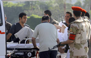 Photo - Egyptian medics and military policemen escort former Egyptian President Hosni Mubarak, 85, into an ambulance after after he was flown by a helicopter ambulance to the Maadi Military Hospital from Torah prison in, Cairo, Egypt, Thursday, Aug. 22, 2013. Egypt's ousted leader Hosni Mubarak has been released from jail and taken to military hospital in Cairo. (AP Photo/Amr Nabil)