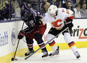 photo - Columbus Blue Jackets' Vinny Prospal (22), of the Czech Republic, keeps the puck away from Calgary Flames' Blair Jones during the second period of an NHL hockey game, Thursday, Feb. 7, 2013, in Columbus, Ohio. (AP Photo/Jay LaPrete)