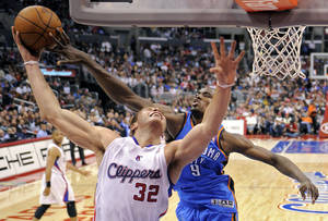 Photo - Oklahoma City Thunder power forward Serge Ibaka, right, of Congo tries to block the shot of Los Angeles Clippers power forward Blake Griffin during the first half of their NBA basketball game, Saturday, April 2, 2011, in Los Angeles. AP Photo