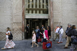 Photo - In this Monday, May 19, 2014 photo, shoppers walk by Tiffany & Company's Fifth Avenue store in New York. The upscale jeweler known for its blue boxes reports earnings Wednesday, May 21, 2014. (AP Photo/Mark Lennihan)