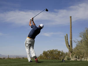 Photo - Graeme McDowell watches his tee shot on the second hole during a practice round at the Match Play Championship golf tournament on Tuesday, Feb. 18, 2014 in Marana, Ariz. (AP Photo/Chris Carlson)