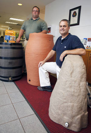 Photo - Edmond Water Resources Superintendent Kris Neifing, left, and Phil Jones, sustainability planner, display water storage containers that will be available to customers in Edmond.  Photo by Paul Hellstern, The Oklahoman