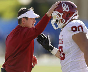 Photo - Oklahoma coach Bob Stoops taps the helmet of OU's Matt Dimon (90) after a punt block during the college football game between the University of Oklahoma Sooners (OU) and the University of Kansas Jayhawks (KU) at Memorial Stadium in Lawrence, Kan., Saturday, Oct. 19, 2013. Oklahoma won 34-19. Photo by Bryan Terry, The Oklahoman