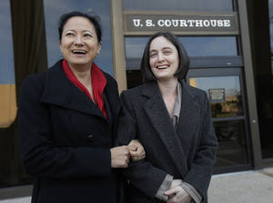 Photo - File - In this Feb. 12, 2014 file photo, Cleopatra De Leon, left, and partner, Nicole Dimetman, right, arrive at the U.S. Federal Courthouse, in San Antonio, where a federal judge is expected to hear arguments in a lawsuit challenging Texas' ban on same-sex marriage. On Wednesday, Feb. 26, 2014, Judge Orlando Garcia has struck down  the ban but is leaving it in place pending a ruling by an appeals court later this year. (AP Photo/Eric Gay, File)