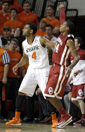 Photo - Oklahoma's Buddy Hield, right, watches his three-point shot in front of Oklahoma State's Brian Williams during Saturday's game. Hield led the Sooners with 22 points, including five 3-pointers.  Photo by Sarah Phipps, The Oklahoman