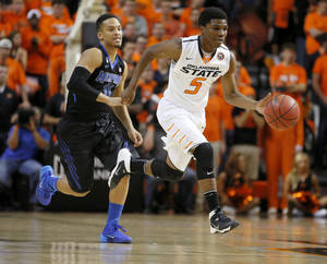 Photo - OSU's Stevie Clark, right, dribbles past Memphis' Michael Dixon Jr. during a game earlier this season. Clark has been suspended indefinitely.  Photo by Bryan Terry, The Oklahoman