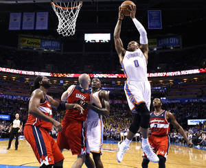 Photo - Oklahoma City's Russell Westbrook (0) shoots a lay up during the NBA game between the Oklahoma City Thunder and the Washington Wizards at the Chesapeake Energy Arena, Sunday, Nov. 10, 2013. Photo by Sarah Phipps, The Oklahoman