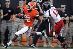 photo - Oklahoma State&#039;s Isaiah Anderson (82) makes a touchdown catch past Texas Tech&#039;s D.J. Johnson (12) during the college football game between the Oklahoma State University Cowboys (OSU) and Texas Tech University Red Raiders (TTU) at Boone Pickens Stadium on Saturday, Nov. 17, 2012, in Stillwater, Okla.   Photo by Chris Landsberger, The Oklahoman