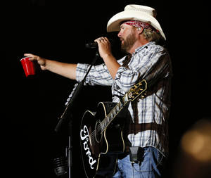 Photo - Toby Keith speaks to the crowd during the Oklahoma Twister Relief Concert, benefiting victims of the May tornadoes, at Gaylord Family - Oklahoma Memorial Stadium on the campus of the University of Oklahoma in Norman, Okla., Saturday, July 6, 2013. Photo by Nate Billings, The Oklahoman