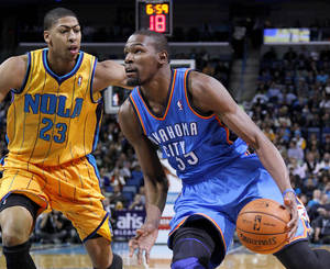 Photo - Oklahoma City Kevin Durant (35) drives against New Orleans Anthony Davis (23) during the first half of an NBA basketball game in New Orleans, Friday, Nov. 16, 2012. (AP Photo/Jonathan Bachman) ORG XMIT: LAJB105