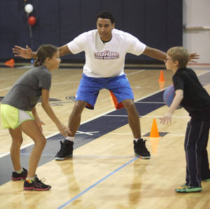 Photo - Oklahoma City Thunder forward Josh Huestis works with students as he visits this week's Thunder Youth Basketball camp at Casady School in Oklahoma City, OK, Thursday, July 17, 2014,  Photo by Paul Hellstern, The Oklahoman