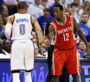 Photo - Oklahoma City's Russell Westbrook, left, brushes away the hand of Houston's Patrick Beverley after Westbrook got up from being knocked to the floor as Beverley defended him during Game 2 on Wednesday. Photo by Nate Billings, The Oklahoman
