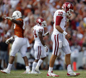 Photo - OU's Blake Bell (10) walks off the field after throwing an interception during the Red River Rivalry college football game between the University of Oklahoma Sooners (OU) and the University of Texas Longhorns (UT) at the Cotton Bowl Stadium in Dallas, Saturday, Oct. 12, 2013. Photo by Chris Landsberger, The Oklahoman