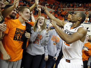 photo - Oklahoma State 's Markel Brown (22) celebrates the 67-69 overtime win over Baylor with the fans during the college basketball game between the Oklahoma State University Cowboys (OSU) and the Baylor University Bears (BU) at Gallagher-Iba Arena on Wednesday, Feb. 5, 2013, in Stillwater, Okla. Photo by Chris Landsberger, The Oklahoman