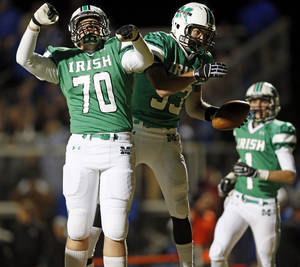 photo - Dan Christiansen (70) and Danny Krenger (33) of Bishop McGuinness celebrate a touchdown catch by Krenger in the first quarter during a high school football game between Bishop McGuinness and Guthrie at Bishop McGuinness Catholic High School in Oklahoma City, Friday, Oct. 26, 2012. Photo by Nate Billings, The Oklahoman