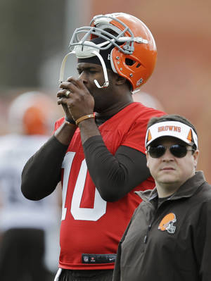 Photo - Cleveland Browns quarterback Vince Young warms his hands during a voluntary minicamp workout at the NFL football team's facility in Berea, Ohio Thursday, May 1, 2014. (AP Photo/Mark Duncan)