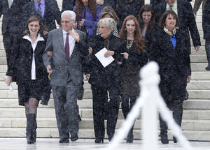 Photo - David Green, founder and chief executive officer of Hobby Lobby, second from left, walks with his wife Barbara, center, and members of their family as they acknowledge a cheer from demonstrators in the crowd as they descend the steps of the Supreme Court in Washington.    AP File Photo <strong>Charles Dharapak -  AP </strong>