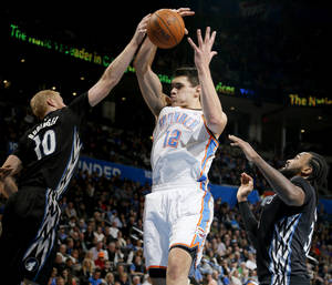 Photo - Oklahoma City's Steven Adams (12) goes for a rebound between Minnesota's Chase Budinger (10) and Dante Cunningham (33) during an NBA basketball game between the Oklahoma CIty Thunder and the Minnesota Timberwolves at Chesapeake Energy Arena in Oklahoma City, Wednesday, Feb. 5, 2014. Photo by Bryan Terry, The Oklahoman