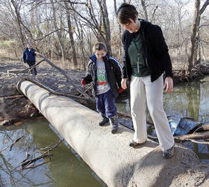 photo - Naturalist Casey Lindo, right, and Zachary Miller cross a creek at Martin Park Nature Center. Much of the park is not accessible to people with disabilities. PHOTO BY NATE BILLINGS, the OKLAHOMAN ARCHIVEs