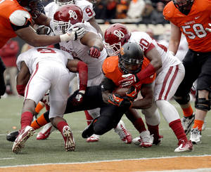 Photo - Oklahoma State's Desmond Roland (26) is stopped short of the goal line by Oklahoma's Frank Shannon (20) during the Bedlam college football game between the Oklahoma State University Cowboys (OSU) and the University of Oklahoma Sooners (OU) at Boone Pickens Stadium in Stillwater, Okla., Saturday, Dec. 7, 2013. OU won 33-24. Photo by Sarah Phipps, The Oklahoman