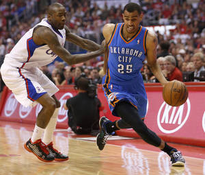 Photo - Oklahoma City's Thabo Sefolosha (25) goes past Los Angeles' Jamal Crawford (11) during Game 4 of the Western Conference semifinals in the NBA playoffs between the Oklahoma City Thunder and the Los Angeles Clippers at the Staples Center in Los Angeles, Sunday, May 11, 2014. Photo by Nate Billings, The Oklahoman
