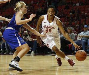 Photo - Oklahoma's Gioya Carter (25) drives the ball past Creighton's McKenzie Fujan (11) during the first half of an NCAA college basketball game in Norman, Okla., Sunday, Dec. 1, 2013. (AP Photo/Garett Ray Fisbeck)