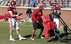 Photo - Blake Bell (10) and Dimitri Flowers (36) get personal attention during blocking drills as the University of Oklahoma Sooners (OU) begin spring practice on Owen Field at Gaylord Family-Oklahoma Memorial Stadium in Norman, Okla., on Tuesday, March 11, 2014. Photo by Steve Sisney, The Oklahoman
