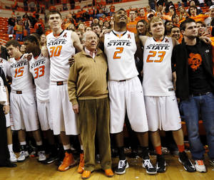 Photo - Boone Pickens, middle, sings the alma mater with the OSU Cowboys including, from left, Christien Sager (15), Marcus Smart (33), Mason Cox (30), Le'Bryan Nash (2) and Alex Budke (23) after a men's college basketball game between Oklahoma State University and the University of Texas at Gallagher-Iba Arena in Stillwater, Okla., Saturday, March 2, 2013. OSU won, 78-65. Photo by Nate Billings, The Oklahoman