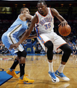Photo - Oklahoma City's Kevin Durant (35) takes the ball past Denver's Randy Foye (4) during an NBA basketball game between the Oklahoma City Thunder and the Denver Nuggets at Chesapeake Energy Arena in Oklahoma City, Monday, Nov. 18, 2013. Photo by Nate Billings, The Oklahoman