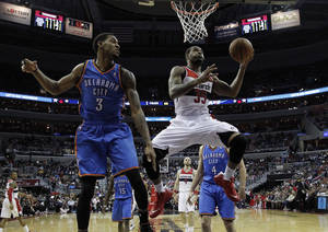 Photo - Washington Wizards forward Trevor Booker (35) shoots with Oklahoma City Thunder forward Perry Jones (3) nearby n the second half of an NBA basketball game on Saturday, Feb. 1, 2014, in Washington. The Wizards won 96-81. (AP Photo/Alex Brandon)